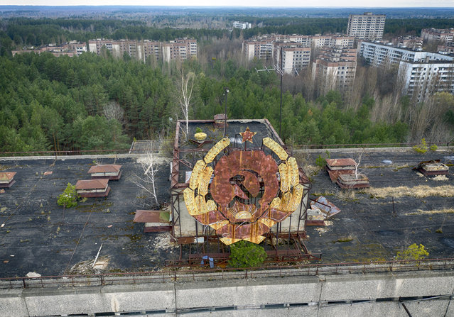 The rusty emblem of the Soviet Union is seen over the ghost town of Pripyat close to the Chernobyl nuclear plant, Ukraine, Thursday, April 15, 2021. The vast and empty Chernobyl Exclusion Zone around the site of the world's worst nuclear accident is a baleful monument to human mistakes. Yet 35 years after a power plant reactor exploded, Ukrainians also look to it for inspiration, solace and income. (Photo by Efrem Lukatsky/AP Photo)