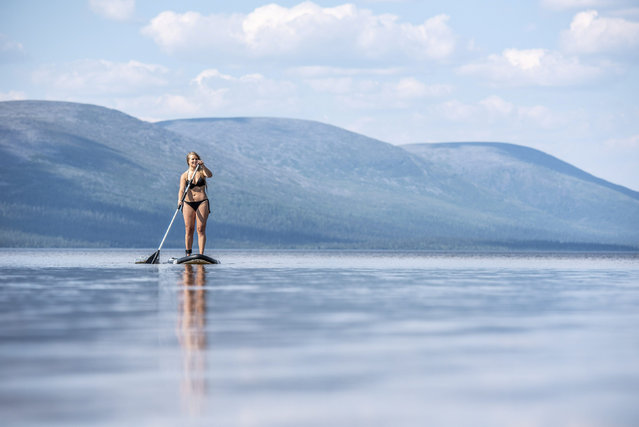 A woman enjoys the warm weather while paddling on the Pallasjarvi lake in Kittila, Lapland, Finland July 18, 2018. (Photo by Otto Ponto/Reuters/Lehtikuva)