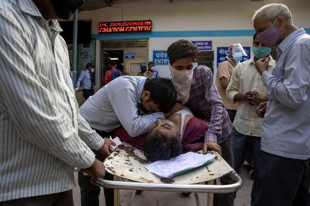 Family members mourn after Shayam Narayan is declared dead outside the coronavirus disease (COVID-19) casualty ward, at Guru Teg Bahadur hospital, amidst the spread of the disease in New Delhi, India, April 23, 2021. (Photo by Danish Siddiqui/Reuters)