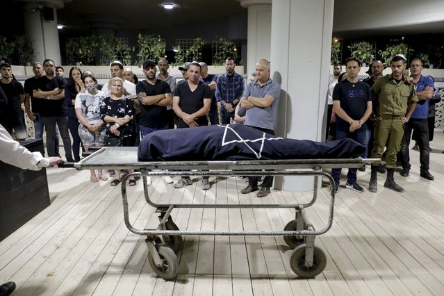 Mourners attend the funeral of Leah Yom Tov, 63, at a cemetery in Rishon Lezion, Israel, Wednesday, May 12, 2021. Yom Tov was killed from a rocket that was fired from Gaza Strip and hit her house in Rishon Lezion on May 11. (Photo by Sebastian Scheiner/AP Photo)