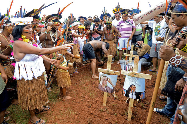 Brazilian natives simulate the burial of politicians during a demonstration in front of the National Congress in Brasilia on October 3, 2013. Indigenous people from several ethnic groups concentrate in the Brazilian capital to demand more support from the federal government during the National Indigenous Mobilization Week. (Photo by Evaristo Sa/AFP Photo)