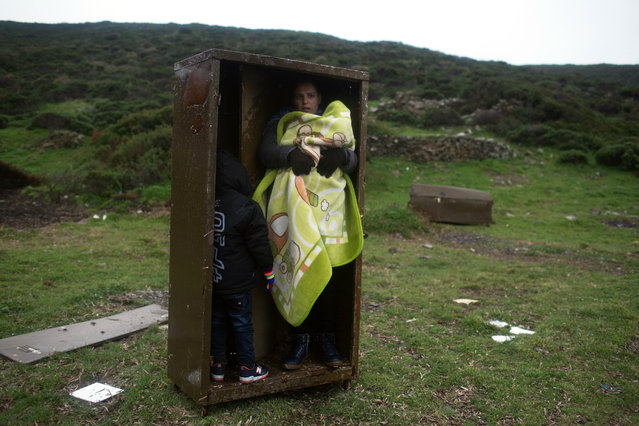 A Syrian woman with her children takes a shelter in a iron box during a rainfall, after they arrived from Turkey to the Greek deserted island of Pasas near Chios on Wednesday, January 20, 2016 . Thousand of migrants and refugees continue to reach Greece's shores despite the winter weather. (Photo by Petros Giannakouris/AP Photo)