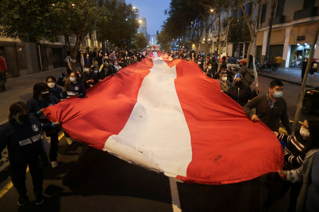 Protestors march with an oversized Peruvian flag against Peru's presidential candidate Keiko Fujimori during a demonstration ahead of the June 6 run-off election between Fujimori and Pedro Castillo, in Lima, Peru on June 1, 2021. (Photo by Sebastian Castaneda/Reuters)