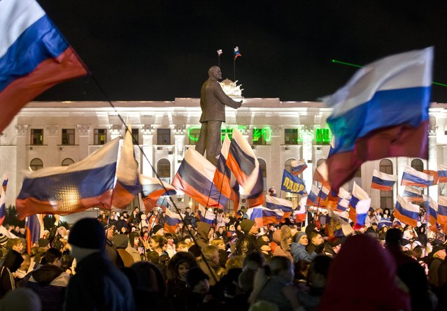In this Sunday, March 16, 2014 file photo pro-Russian people with Russian flags celebrate a referendum on seceding from Ukraine and seeking annexation by Russia, in Lenin Square in Simferopol, Crimea. (Photo by Vadim Ghirda/AP Photo)