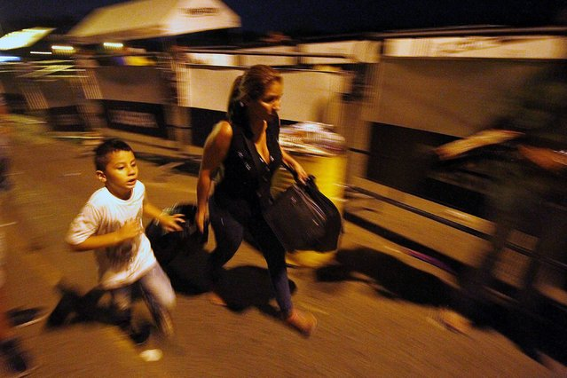 "A woman and a boy run across the Simon Bolivar bridge on the Colombian border with Venezuela, on December 12, 2016. Venezuelan President Nicolas Maduro on Monday ordered the border with Colombia sealed for 72 hours, accusing US-backed ""mafias"" of conspiring to destabilize his country's economy by hoarding bank notes. The closure came a day after Maduro signed an emergency decree removing Venezuela's largest bank note, the 100 bolivar bill, from circulation because of what he called a Washington-sponsored plot against his country's troubled economy. (Photo by Schneyder Mendoza/AFP Photo)"