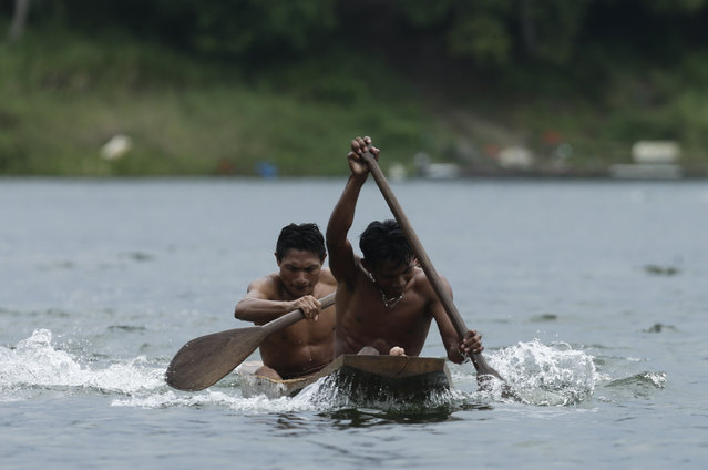 In this November 25, 2018 photo, two Guna indigenous men row in the dugout canoe competition during the second edition of the Panamanian indigenous games on Lake Bayano, Panama. Lake Bayano is one of the main reservoirs in Panama. (Photo by Arnulfo Franco/AP Photo)
