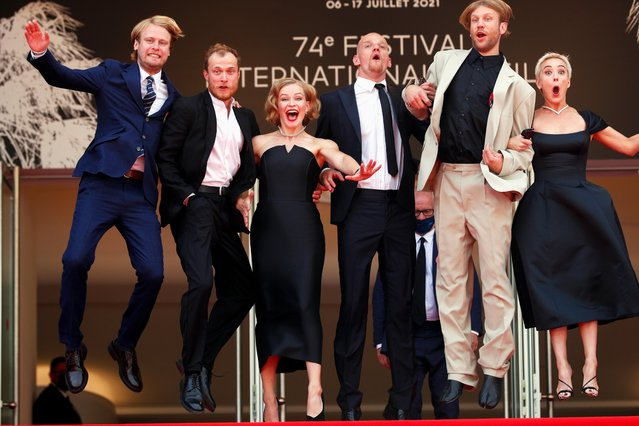 """(L-R) Russian actor Semyon Serzin, Russian actor Yuriy Borisov, Russian actress Yuliya Peresild, Russian actor Yuri Kolokolnikov, Russian actor Ivan Dorn and Russian actress Chulpan Khamatova jump as they arrive for the screening of the film """"Petrov's Flu"""" at the 74th edition of the Cannes Film Festival in Cannes, southern France, on July 12, 2021. (Photo by Johanna Geron/Reuters)"""