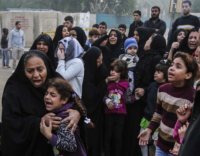 Mourners grieve for a man killed Monday in a bombing at a cafe in Sadriyah, a predominantly Shiite area of Baghdad, Iraq, on November 26, 2013. Officials in Iraq say scores have been killed in a double bombing at a market and other attacks across Iraq on Monday. (Photo by Karim Kadim/Associated Press)