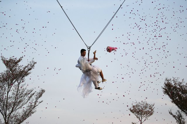 Groom Major Thipilindhra Chidee and his bride Laddawal Chaidee throw a bouquet as they fly while attached to cables during a wedding ceremony ahead of Valentine's Day at a resort in Ratchaburi province, Thailand, February 13, 2016. (Photo by Athit Perawongmetha/Reuters)