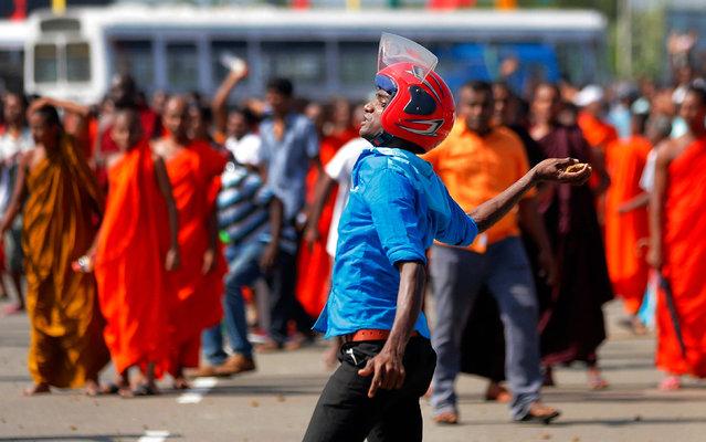 A Sri Lankan protester hurls a stone at government supporters during a protest in Mirijjawila village in Ambalantota, Sri Lanka, Saturday, January 7, 2017. (Photo by Eranga Jayawardena/AP Photo)