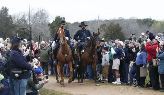 A re-enactor portraying Union General Ulysses S. Grant, right, and a fellow officer arrive at the McLean house to meet with Confederate General Robert E. Lee during the commemoration of the 150th anniversary of the surrender of the Army of Northern Virginia at Appomattox Court House, Thursday, April 9, 2015, in Appomattox, Va. (Photo by Steve Helber/AP Photo)