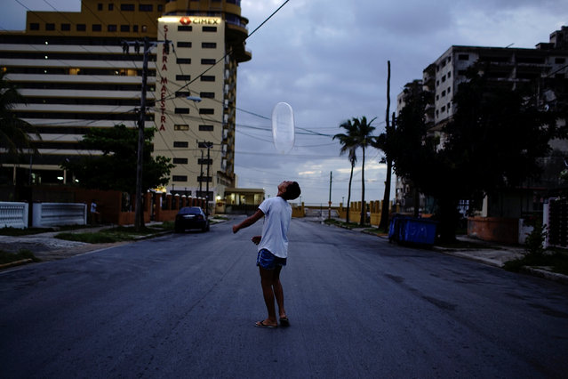 Arturo Perez, 14, plays on the street with a condom in Havana, Cuba, August 27, 2018. (Photo by Alexandre Meneghini/Reuters)