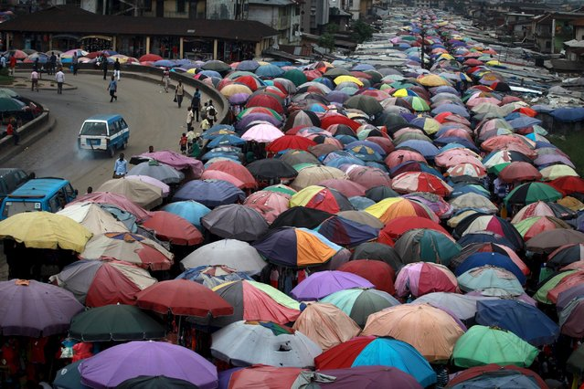 Street traders covers stalls with umbrellas along abandoned railway line in Nigeria's oil hub city of Port Harcourt in this December 3, 2012 file photo.   Nigeria is expected to report GDP output data this week. (Photo by Akintunde Akinleye/Reuters)