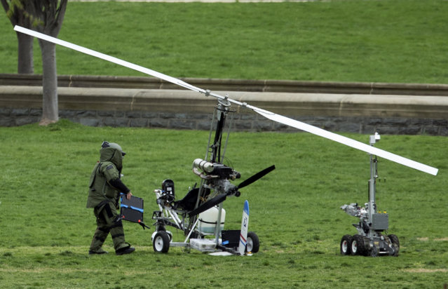 A member of a bomb squad checks a small helicopter after a man landed on the West Lawn of the Capitol in Washington, Wednesday, April 15, 2015. Police arrested a man who steered his tiny, one-person helicopter onto the West Lawn of the U.S. Capitol Wednesday, astonishing spring tourists and prompting a temporary lockdown of the Capitol Visitor Center. (Photo by Manuel Balce Ceneta/AP Photo)