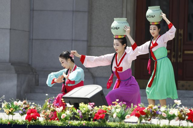 An art troupe performs in front of the Pyongyang Grand Theatre in Pyongyang, North Korea, Tuesday, July 27, 2021, to mark the Korean War armistice anniversary. (Photo by Cha Song Ho/AP Photo)