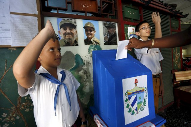 Schoolboys salute as a man casts his vote at a polling station in Havana April 19, 2015. (Photo by Reuters/Stringer)