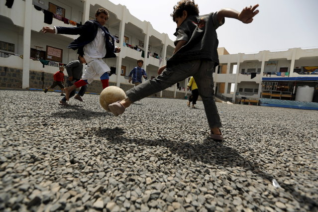 Boys play soccer at the yard of a school sheltering people displaced by Saudi-led air strikes on Yemen's northwestern province of Saada, in the capital Sanaa May 27, 2015. (Photo by Khaled Abdullah/Reuters)