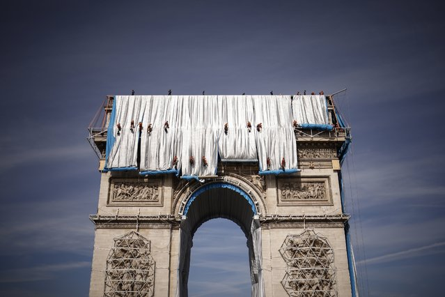 """Steeplejacks work on the assembly of the """"Arc de Triomphe"""" wrapping as part of an art installation by the late artist Christo, in Paris, France, 12 September 2021. The monumental installation will wrap the landmark Parisian monument under a 25,000 square meters silver and blue fabric from 18 September to 03 October 2021 despite the Bulgarian-born US artist Christo's death in May 2020. (Photo by Yoan Valat/EPA/EFE)"""