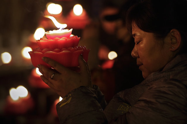 A woman holds a flower-shape candle prays on the first day of the Chinese Lunar New Year at the Tanzhe temple in the Mentougou District of Beijing, Tuesday, February 5, 2019. Chinese people are celebrating the arrival of the Lunar New Year, the Year of the Pig on the Chinese zodiac. (Photo by Andy Wong/AP Photo)
