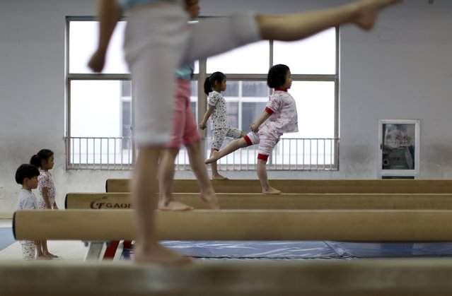 Young gymnasts practice on balance beams at a gymnasium of a sports school in Jiaxing, Zhejiang province, April 17, 2015. (Photo by William Hong/Reuters)