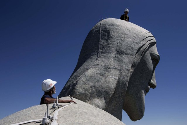 Repair workers examine the Christ Redeemer statue on January 21, 2014. (Photo by Felipe Dana/Associated Press)