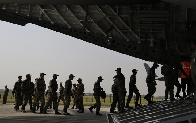 Indian soldiers on rescue mission to Nepal, board an Indian Air Force aircraft near New Delhi, India, Sunday, April 26, 2015. (Photo by Altaf Qadri/AP Photo)
