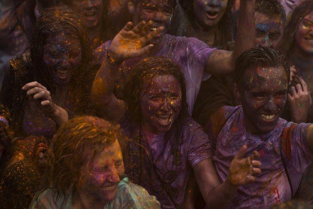 Revelers shout during a Holi Festival in Madrid, Spain, Sunday, April 26, 2015. (Photo by Andres Kudacki/AP Photo)
