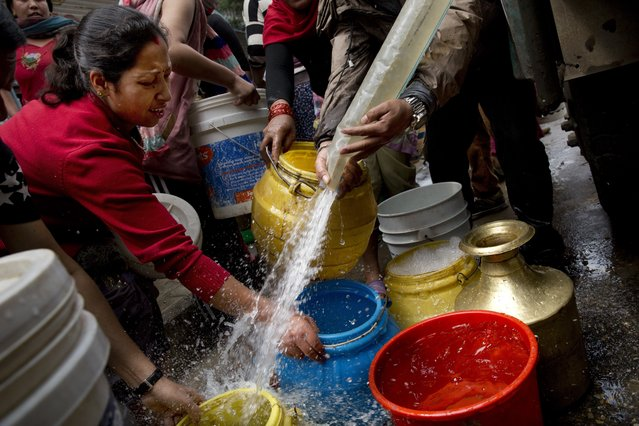 Nepalese collect water distributed in a tanker in Kathmandu, Nepal, Wednesday, April 29, 2015. While many villages across Nepal affected by Saturday's earthquake are still waiting for rescue and relief teams, life in the capital, Kathmandu, is slowly returning to normal. (Photo by Bernat Amangue/AP Photo)