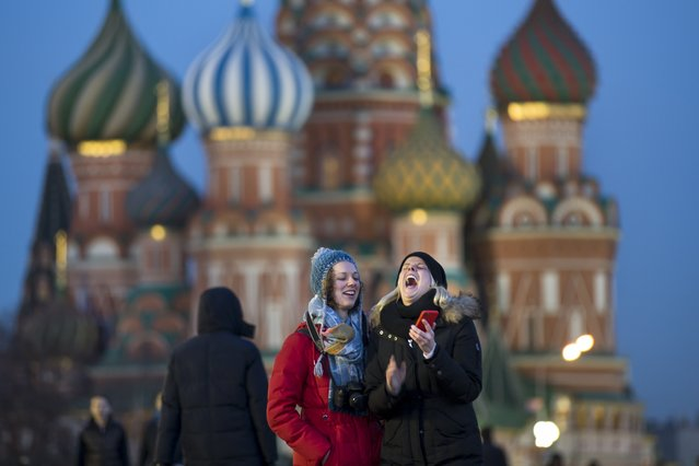 Tourists take a selfie in front of St. Basil Cathedral in Red Square in Moscow, Russia, Thursday, March 10, 2016.  (Photo by Alexander Zemlianichenko/AP Photo)