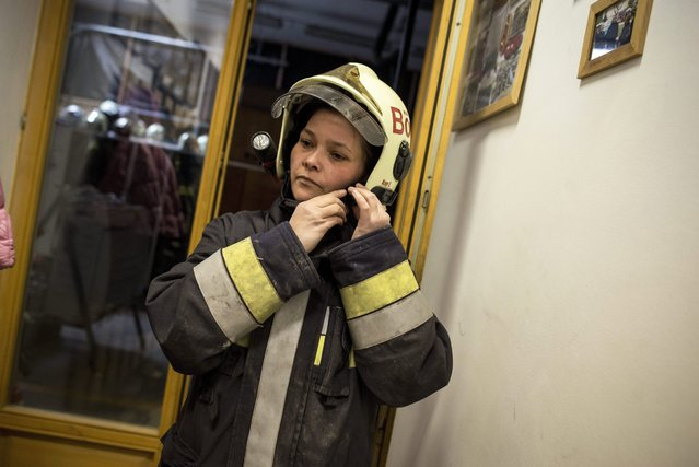 Volunteer firefighter Eniko Nagy fastens her helmet in the Budaors Fire Services Department building in Budaors, a south western suburb of Budapest, Hungary, 05 March 2016. (Photo by Bea Kallos/EPA)