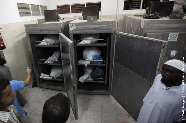 Palestinians stand in the morgue next to the bodies of six militants killed in an Israeli airstrike
