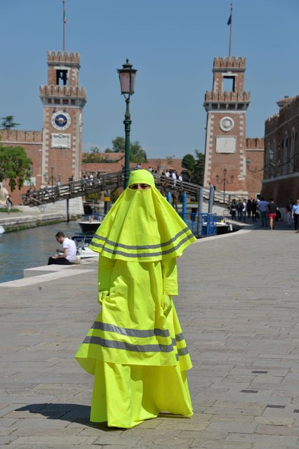 """A model wears a dress called """"High Visibility Burqa"""" during a performance of Italian artist Marco Biagini during the 56th Biennale of Arts in Venice, Italy, May 8, 2015. (Photo by Andrea Merola/EPA)"""