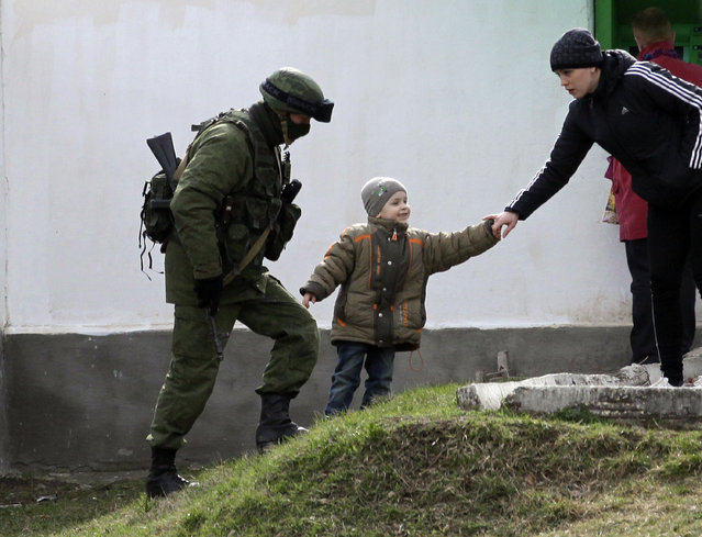A Russian soldier on patrol passes by a child playing with his mother in front of the Ukraine's infantry base in Perevalne, Ukraine, Tuesday, March 4, 2014. (Photo by Darko Vojinovic/AP Photo)
