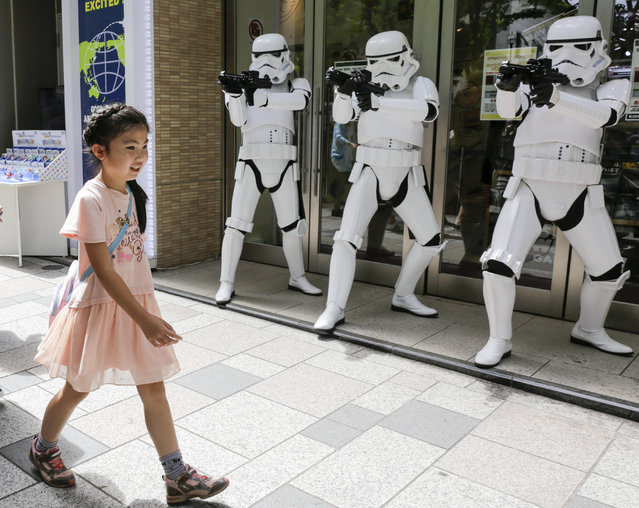 """A girl walks past Star Wars' Stormtroopers posing in an appearance for a campaign celebrating """"Star Wars Day"""" at a toy shop in Tokyo, Japan, May 4, 2015. May fourth is commemorated for """"May the Force be with you"""", the famous words in the movie. (Photo by Kimimasa Mayama/EPA)"""
