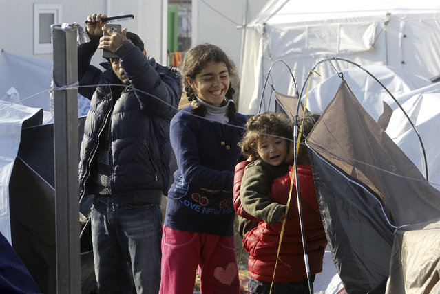 A man combs his hair by looking himself on a mobile phone while children play by their tent at the transit center for refugees near northern Macedonian village of Tabanovce on the border with Serbia, Monday, March 28, 2016. (Photo by Boris Grdanoski/AP Photo)