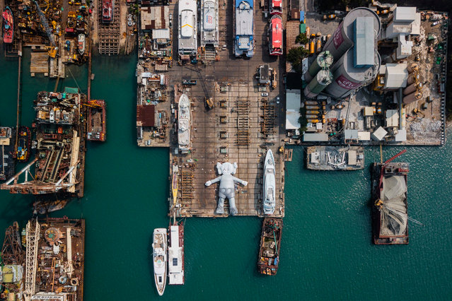 "This aerial photo shows the ""KAWS:HOLIDAY"" ""Companion"" inflatable sculpture (C) by US artist and designer Brian Donnelly, known professionally as Kaws, in a shipyard in Hong Kong on March 11, 2019. Made in collaboration with locally based creative studio AllRightsReserved (ARR), the 37-metre-long (121 ft.) ""KAWS:HOLIDAY"" sculpture will be docked in Victoria Harbour from March 22 to 31 as part of Hong Kong Arts Month. (Photo by Anthony Wallace/AFP Photo)"