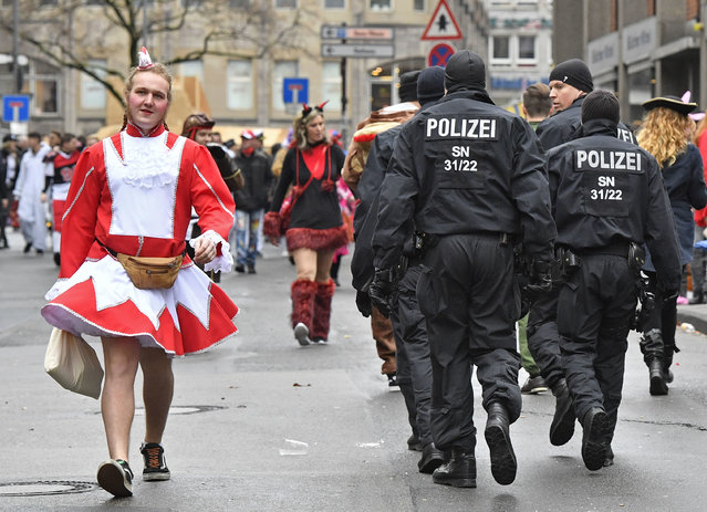 Police patrols when tens of thousands revelers dressed in carnival costumes celebrate the start of the street-carnival in  Cologne, Germany, Thursday, February 23, 2017. (Photo by Martin Meissner/AP Photo)