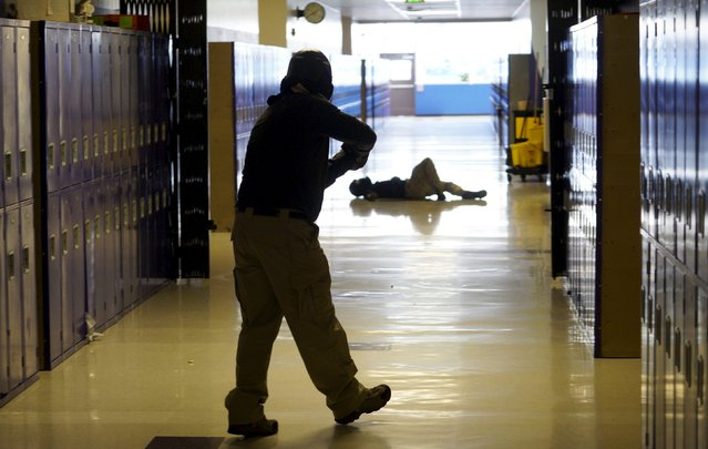 A student searches for a shooter with a mock victim in the background in a middle school during an Active Shooter Response course offered by TAC ONE Consulting in Denver, Colorado April 2, 2016. (Photo by Rick Wilking/Reuters)
