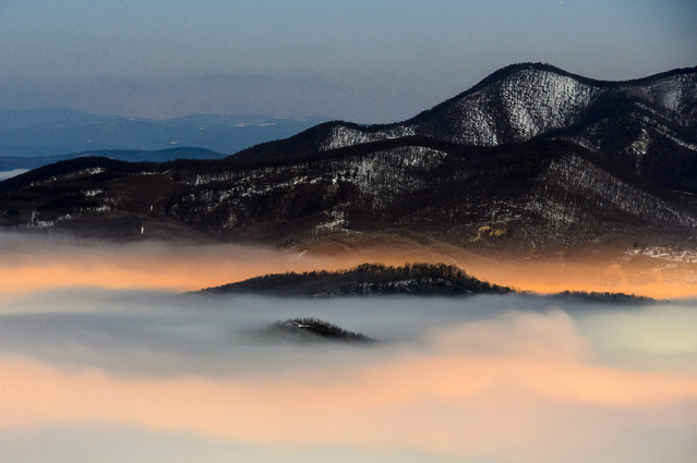 City lights illuminate fog floating above the city of Salgotarjan, 109 kms northeast of Budapest, Hungary, 05 January 2015. Photo was taken from the the 552-meter high Pecsko basalt peak belonging to the city. (Photo by Peter Komka/EPA)