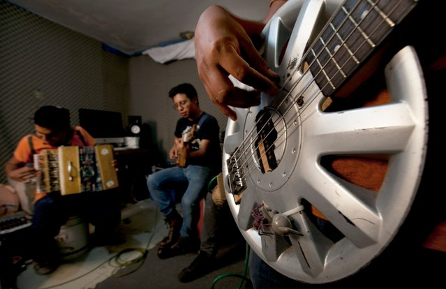 In this Friday, April 24, 2015 photo, Fernando Lopez, left, Oscar De Jesus Ramirez, center, and Jair Cerda Lopez, play their musical instruments made form trash during a jam session at their workshop in the outskirts of Mexico City. (Photo by Marco Ugarte/AP Photo)