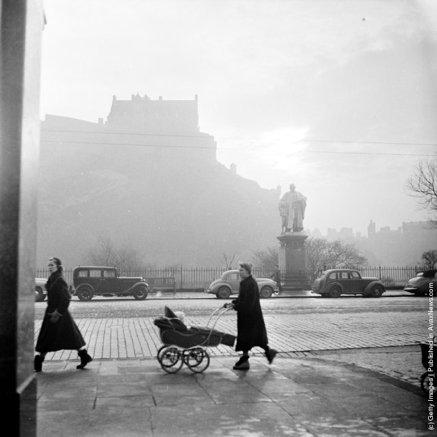 1954: A street scene in Edinburgh with a misty view of the castle in the background