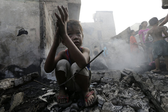 A Filipino boy rests among debris following a pre-dawn fire that razed a slum area in Manila, Philippines, March 23, 2014. Around 150 houses were destroyed at a shantytown leaving more than 200 families homeless. (Photo by Francis R. Malasig/EPA)