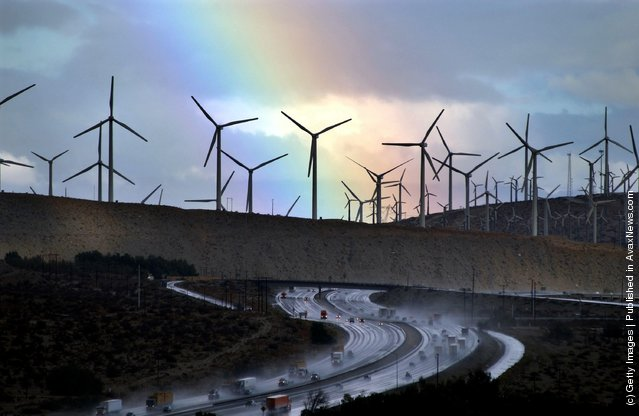 A rainbow forms behind giant windmills near rain-soaked Interstate 10 as an El Nino-influenced storm passes over the state