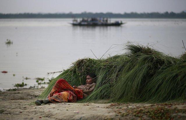 An Indian woman rests on the banks of the River Brahmaputra in Gauhati, India, Thursday, May 21, 2015. (Photo by Anupam Nath/AP Photo)