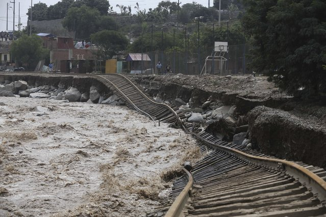 Train tracks lay destroyed in a flooded river in the Chosica district of Lima, Peru, Sunday, March 19, 2017. Intense rains and mudslides over the past three days have wrought havoc around the Andean nation and caught residents in Lima, a desert city of 10 million where it almost never rains, by surprise. (Photo by Martin Mejia/AP Photo)