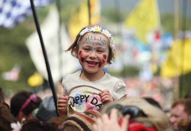 Lexi Owen, 6, from Canterbury watches Lionel Richie perform on the Pyramid stage at Glastonbury music festival on Worthy Farm, Glastonbury, England, Sunday, June 28, 2015. (Photo by Joel Ryan/Invision/AP Photo)