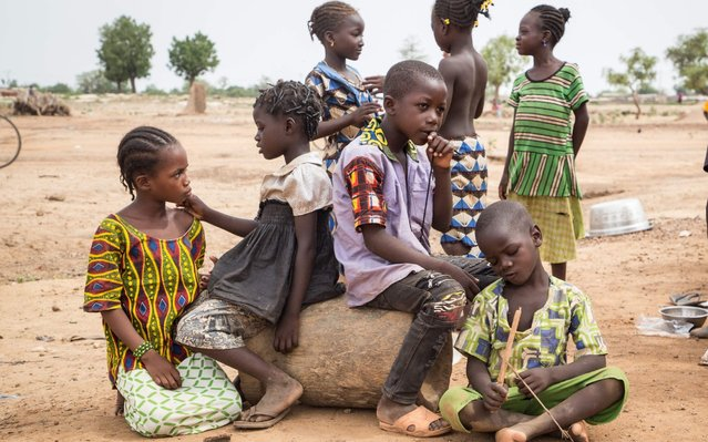 Children stand outside a school used as a shelter for Internally Displaced People (IDP) from northern Burkina Faso on June 13, 2019 in Ouagadougou. Internally Displaced People (IDP) from northern Burkina Faso flee intercommunal clashes, which have already killed a hundred people in a few weeks. (Photo by Olympia De Maismont/AFP Photo)