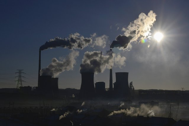 """Smoke rises from chimneys and cooling towers of a thermal power plant during sunrise in Fushun, Liaoning province March 6, 2014. China sent its strongest signal yet that its days of chasing breakneck economic growth were over, promising to wage a """"war"""" on pollution and reduce the pace of investment to a decade-low as it pursues more sustainable expansion. (Photo by Reuters/Stringer)"""