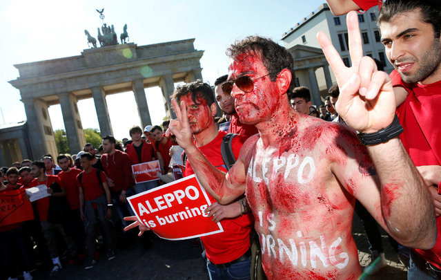 A man with his face and body painted with red colour gestures as they during a rally in solidarity with the people of Aleppo in front of the Brandenburg Gate in Berlin, Germany, May 2, 2016. (Photo by Fabrizio Bensch/Reuters)