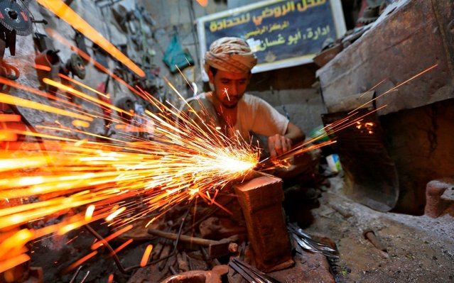 A Yemeni craftsman sharpens knives in the market place of Sanaa's old city, on July 24, 2019. (Photo by Mohammed Huwais/AFP Photo)